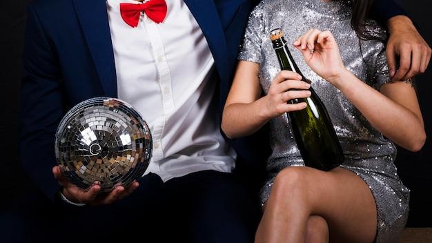 Paar mit discokugel und flasche champagner