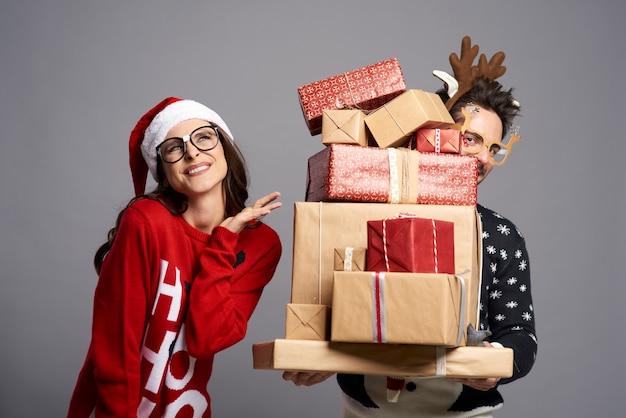 Paar mit einem stapel von erstaunlichen weihnachtsgeschenken
