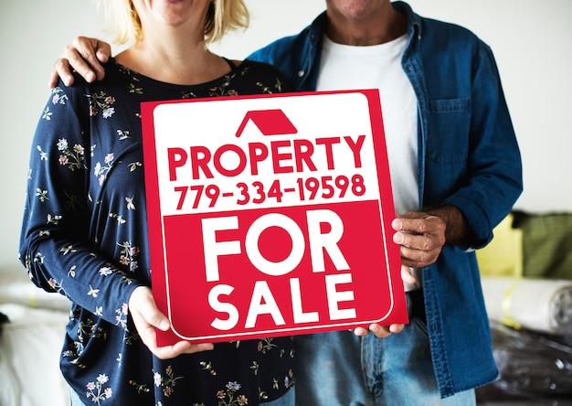 Paar mit einer immobilie zum verkauf zeichen