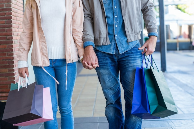 Paar mit einkaufstüten händchen haltend