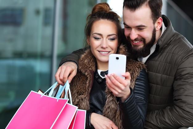 Paar mit einkaufstüten und smartphone in der stadt