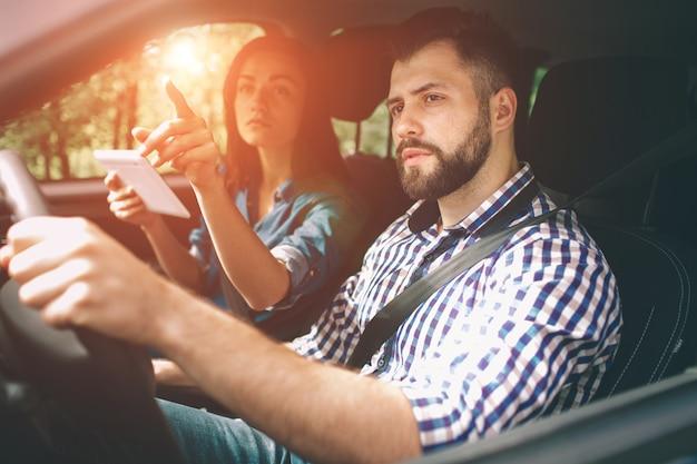 Paar mit gps auf tablet compter, um im urlaub im auto zu navigieren