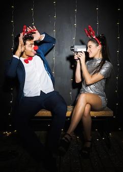 Paar mit hirsch geweih stirnbänder und lustige nasen auf video festhalten
