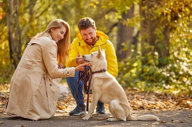 Paar mit hund zu fuß. positives kaukasisches paar genießt, zeit mit hund im wald zu verbringen