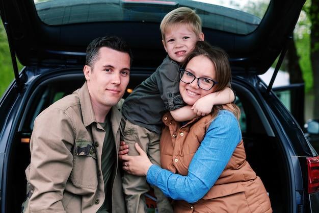 Paar mit ihrem kleinen sohn im offenen kofferraum eines geländewagens auf dem parkplatz