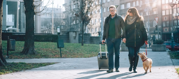 Paar mit koffer und hund zu fuß