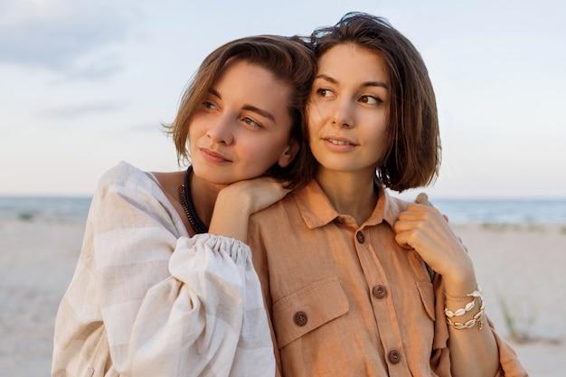Paar mit kurzer frisur in leinensommerkleidung, die am strand aufwirft