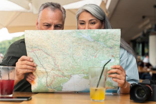 Paar mit mittlerem schuss, das sich die karte anschaut