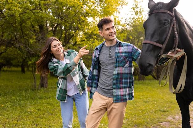 Paar mit mittlerem schuss und pferd im freien