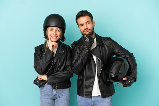 Paar mit motorradhelm über isoliertem blauem hintergrund, der mit einem süßen ausdruck lächelt