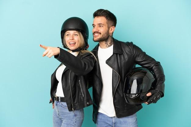 Paar mit motorradhelm über isoliertem blauem hintergrund, der zur seite zeigt, um ein produkt zu präsentieren
