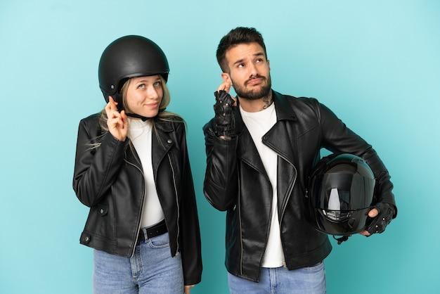 Paar mit motorradhelm über isoliertem blauem hintergrund mit gekreuzten fingern und wünscht das beste