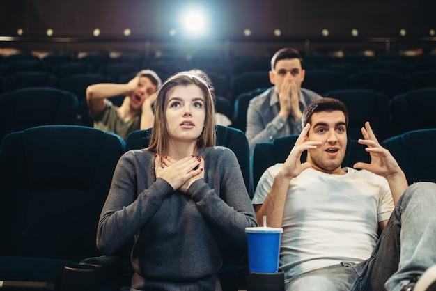 Paar mit popcorn fasziniert den film im kino. showtime, unterhaltungsindustrie