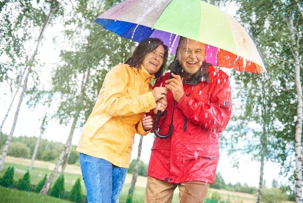 Paar mit regenbogenregenschirm