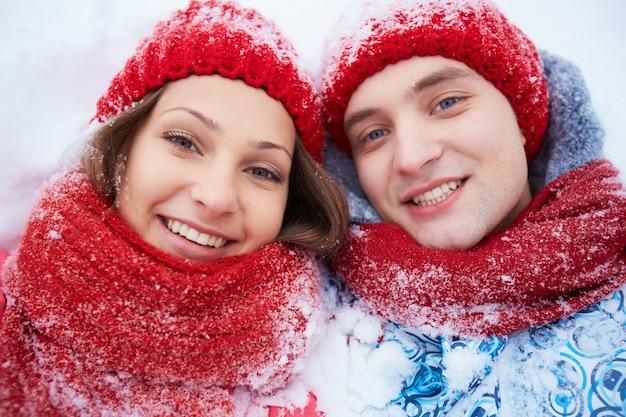 Paar mit roten wollmütze im schnee