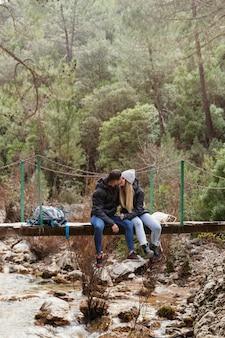 Paar mit rucksack sitzt auf der brücke