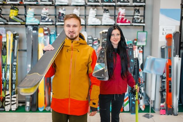 Paar mit skiern in händen, einkaufen im sportgeschäft
