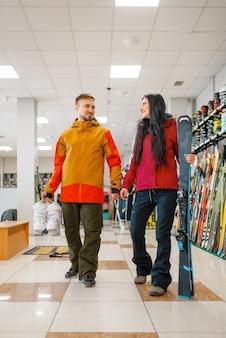 Paar mit skiern und schuhen in händen, sportgeschäft