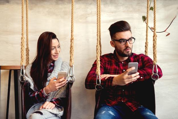 Paar mit smartphones getrennt. zur seite schauen.