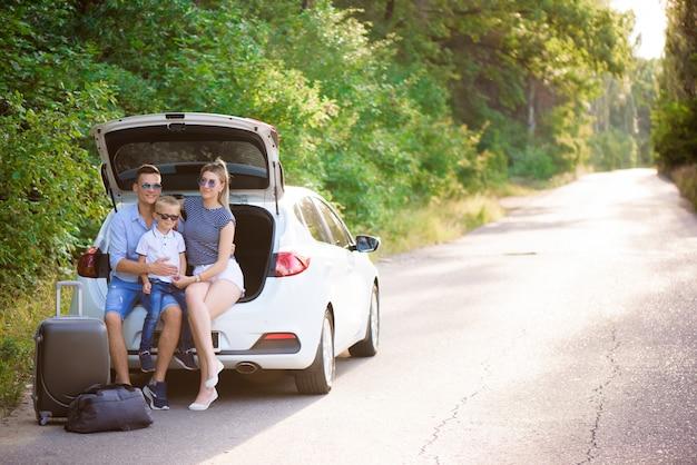 Paar mit sohn, der eine kaffeepause während der reise auf dem land hat. ein mann und eine frau sitzen im kofferraum eines autos und ruhen sich aus.