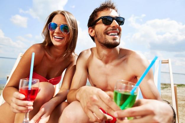 Paar mit sonnenbrille und cocktail am strand