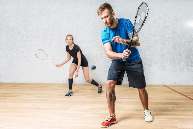 Paar mit squashschlägern, indoor-trainingsclub