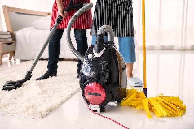 Paar mit staubsauger und mopp, um das schlafzimmer zu hause zu reinigen. hygiene- und gesundheitslebensstilkonzept. hausarbeit am wochenende. elektronische haushaltsmaschine