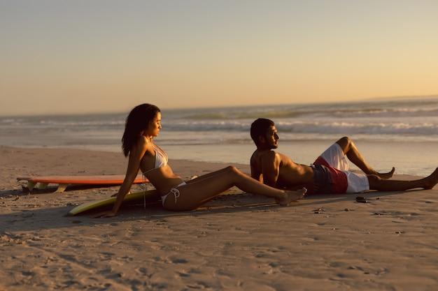 Paar mit surfbrett am strand in der abenddämmerung entspannen