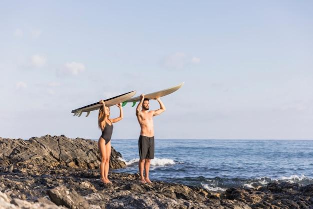Paar mit surfbrettern auf köpfen stehen in der nähe von meer
