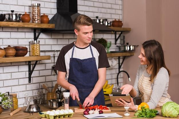 Paar mit tablette in der küche kochen
