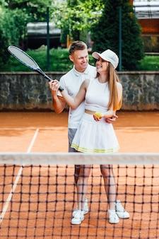 Paar mit tennisschlägern auf außenplatz