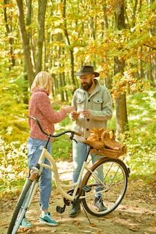 Paar mit vintage-fahrrad-herbstpaar fährt fahrrad im park aktive menschen im freien autu...