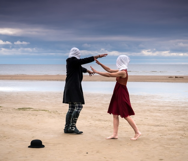 Paar mit völlig geschlossenen köpfen posiert am strand