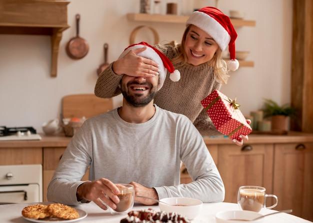 Paar mit weihnachtsmützen drinnen