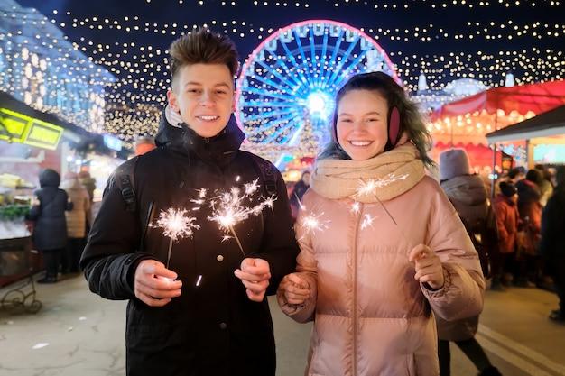 Paar mit wunderkerzen feiern und spaß auf dem weihnachtsmarkt haben