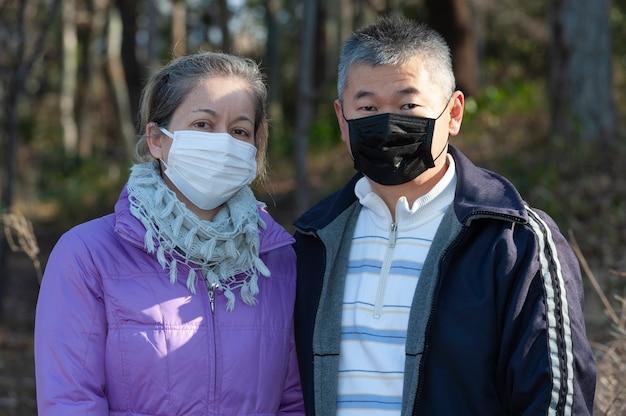 Paar mittleren alters, das eine maske (weiße maske und schwarze maske) zum schutz vor coronavirus trägt