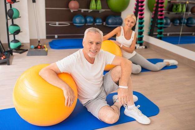 Paar mittleren alters, das zeit im fitnessstudio verbringt und sich positiv fühlt