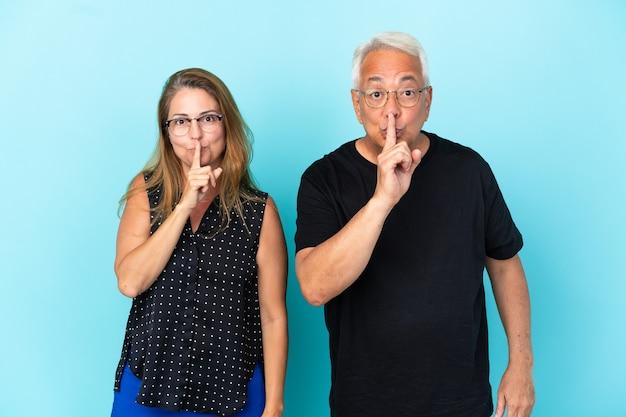 Paar mittleren alters isoliert auf blauem hintergrund, das ein zeichen des schließens des mundes und der stille-geste zeigt