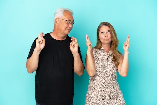 Paar mittleren alters isoliert auf blauem hintergrund mit gekreuzten fingern und wünscht das beste
