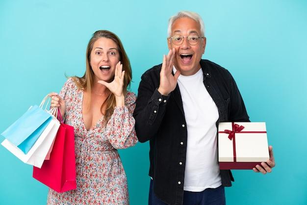 Paar mittleren alters mit einkaufstasche und geschenk einzeln auf blauem hintergrund schreien und etwas ankündigen