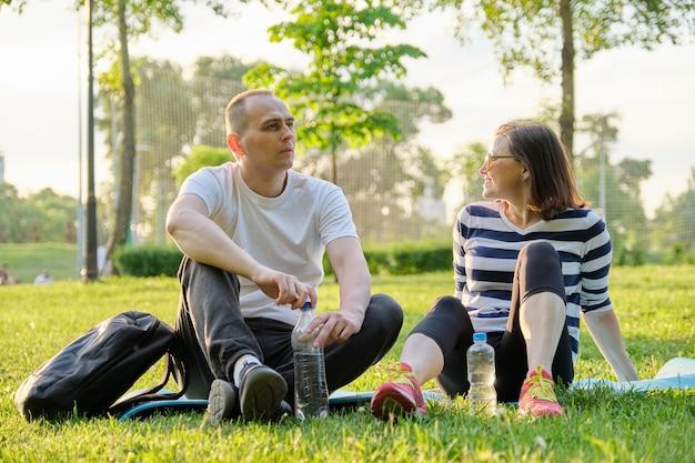 Paar mittleren alters sitzen auf yogamatte, mann und frau sprechen entspannendes trinkwasser. aktiver gesunder lebensstil, beziehung, sport, fitness bei reifen menschen