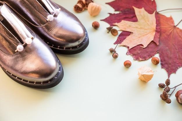 Paar neue frauenschuhe und stiefel bleiben auf pastellfarbenem hintergrund mit fallendem herbstlaub herbstschuhe verkaufshiny lederschuhe weibliche modeschuhe trendige oxford-stiefel