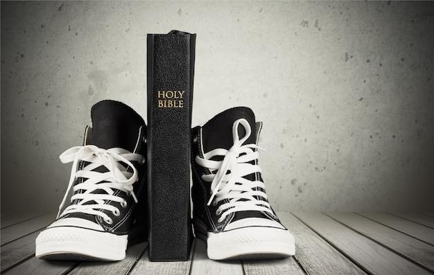 Paar neue schwarze turnschuhe und holly bible auf hintergrund isoliert.