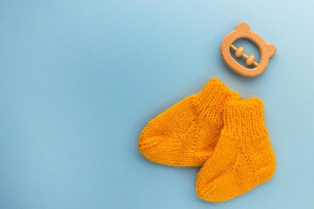 Paar niedliche orange gestrickte babysocken und hölzerner beißringbär auf blau