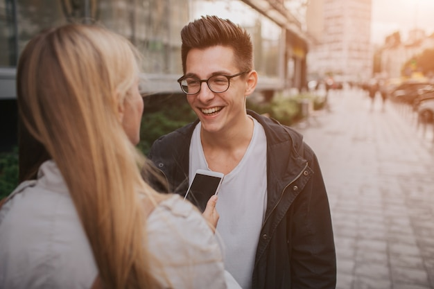 Paar oder freunde, die lustig lachen und spaß mit einem smartphone in einer großstadtstraße haben.