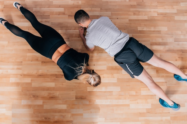 Paar oder trainer unterrichten oder trainieren im fitnessstudio mit plankenaktion. flache lage oder obere ansicht mit kopierraum für text.