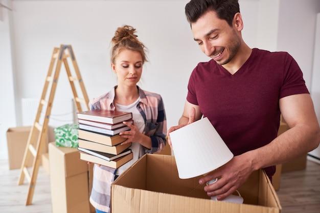 Paar packt bücher und lampe in die kisten