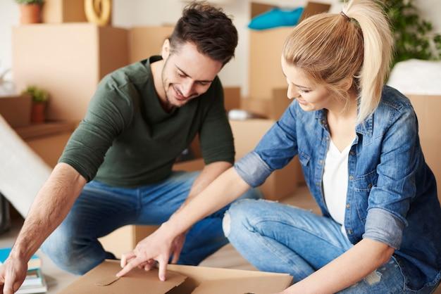 Paar packt kartons im neuen zuhause aus