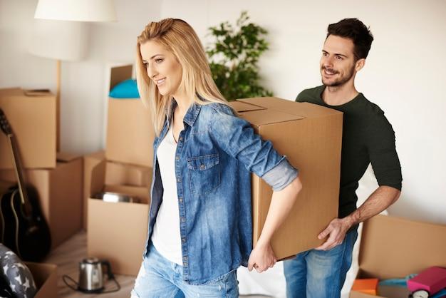 Paar packt kisten in ihrem neuen zuhause aus