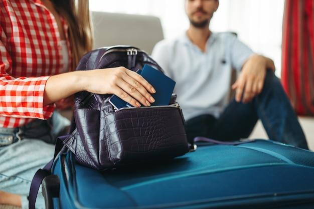 Paar packt seine koffer und nimmt dokumente